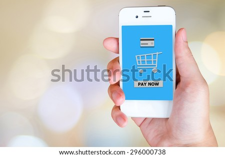 Pay now on smart phone screen in hand with blurred bokeh background, e-business concept