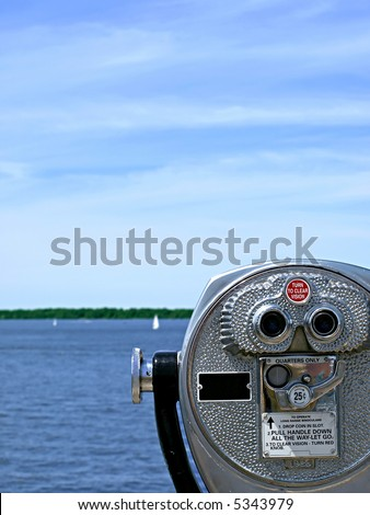 Pay-per-view binoculars look out over a pretty lake with sailboats in the far distance - stock photo