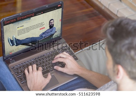 Pay per view concept: Young man at home viewing series streaming web on laptop.