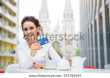 Pay the bill. Beautiful young woman holding plastic credit card while siting in sidewalk cafe. - stock photo