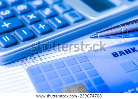 Pay the bills, bank card with a calculator and pen on the table. In blue tone