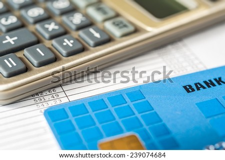 Pay the bills, bank card with a calculator on the table