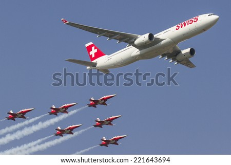PAYERNE, SWITZERLAND - SEPTEMBER 6: Flight of Airbus A-330 and Patrouille Suisse team on AIR14 airshow in Payerne, Switzerland on September 6, 2014