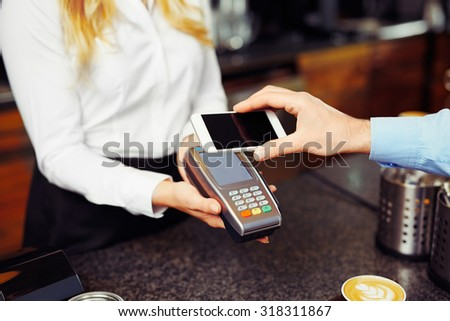 Paying with smartphone. Closeup of man making payment transaction with his mobile phone