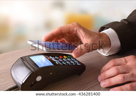 Payment on a trade through mobile and NFC technology. Elevated view. Horizontal composition. - stock photo