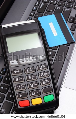 Payment terminal and credit card on laptop keyboard, credit card reader, paying using credit card, finance and banking concept