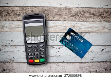 Payment terminal and credit card on wooden background top view - stock photo