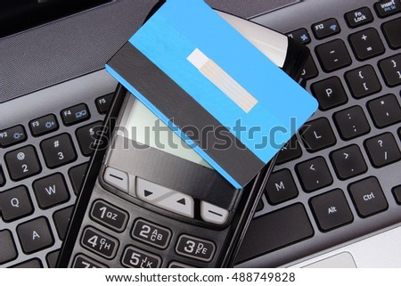 Payment terminal with contactless credit card and laptop, paying using credit card, finance and banking concept