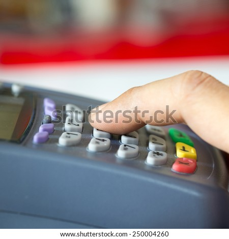 Payment terminal with keypad and a finger pressing on button : Selective Focus