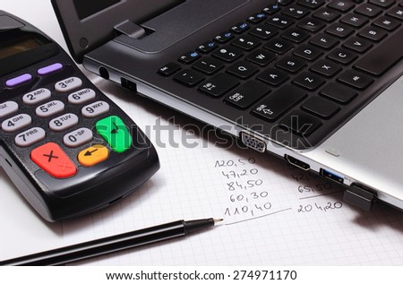 Payment terminal with laptop and financial calculations, credit card reader, finance concept - stock photo