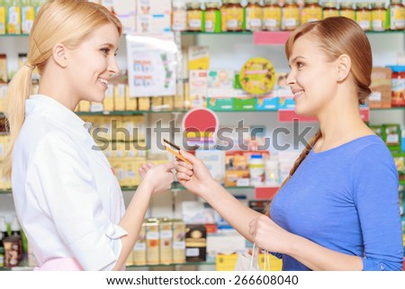Payment with a card. Young smiling customer stretching out a credit card to the nice-looking pharmacist at the pharmacy counter - stock photo