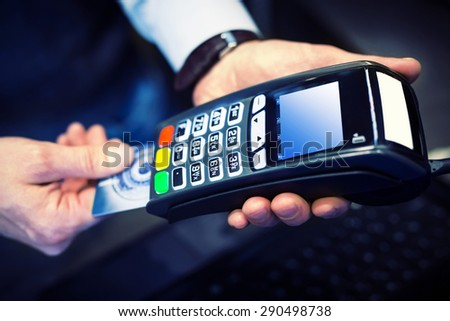 Payment with credit card - man put the credit card into a reader - stock photo