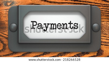 Payments - Inscription on File Drawer Label on a Wooden Background.