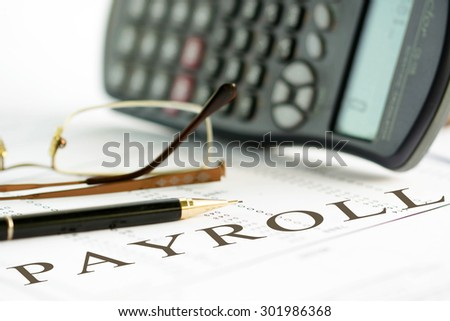 Payroll concept image of a pen, calculator and reading glasses on financial documents. - stock photo