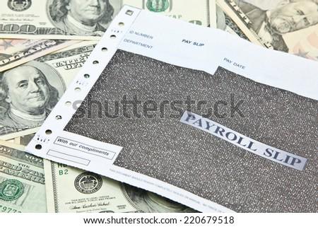 Payroll slip on pile of US dollar banknotes - stock photo