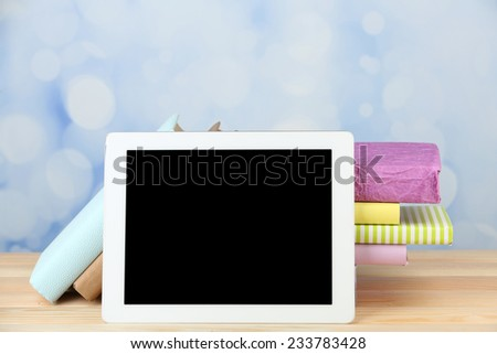 PC tablet and books on wooden table, on light background - stock photo