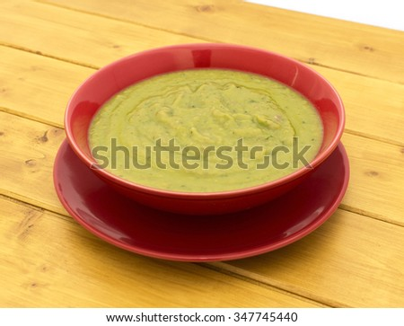 Pea and ham soup in a red bowl on a plate on a wooden table - stock photo