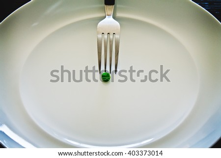 Pea on a white dish with a fork on it - stock photo