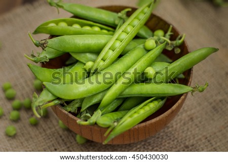 Pea pods in a wooden bowl on sacking. Wooden background. Top view. Close-up - stock photo