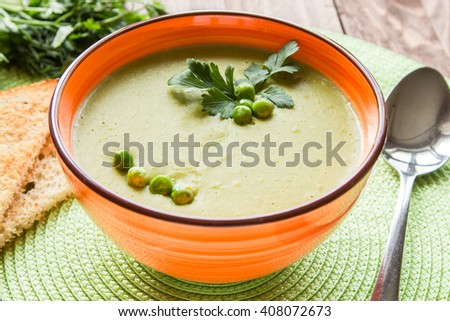 Pea soup in an orange plate with crackers