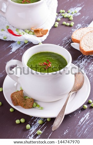 Pea soup in white bowls served with red chili and rye crackers