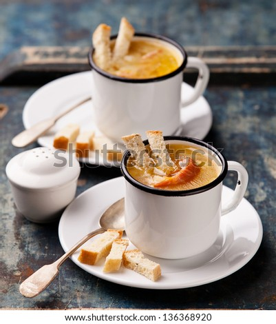 Pea soup with bread and smoked ribs in glass-lined cups