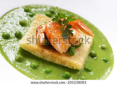 pea soup with prawns in white plate