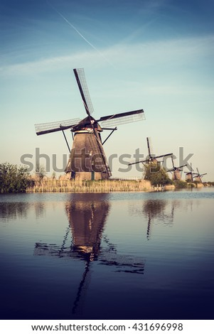 Peace and calm landscape with windmills, sky and reflection in the water, Kinderdijk, Netherlands. Nature hipster vintage instagram background, vertical image - stock photo