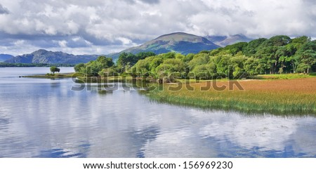 Peace and tranquillity on Lough Leane, Killarney, Ireland, with fluffy white clouds reflected in the calm lake waters. - stock photo