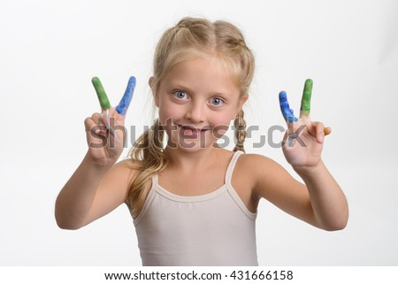 Peace for everyone from little girl who shows special gesture. Funny colorful fingers in paint of different colors. Pleased girl with big blue eyes. - stock photo