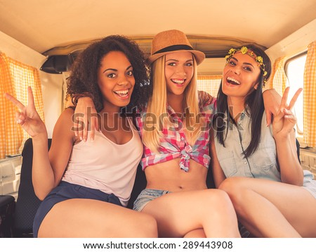 Peace friends! Three excited young women smiling at camera and gesturing while sitting inside of retro minivan  - stock photo