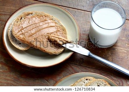 Peace of white bread spread with peanut butter on the plate with glass of milk beside