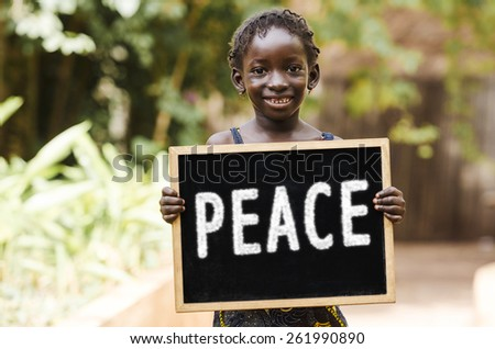 Peace On Earth - African Girl Holding Chalkboard. African child holding a big peace symbol. - stock photo