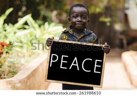 Peace on Earth Symbol - Black Boy Holding Blackboard. A black boy holding a blackboard in the streets of Bamako. - stock photo