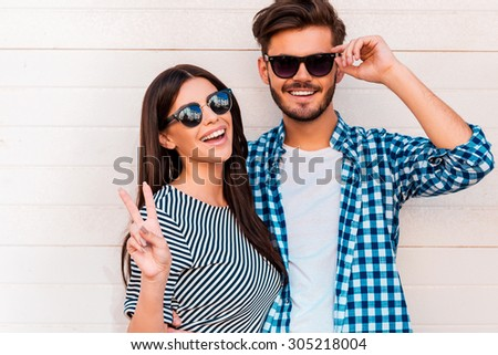 Peace out! Happy young loving couple looking at camera and smiling while standing outdoors - stock photo