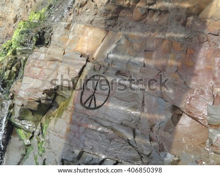 Peace sign carved into rock, with shadows, moss and weathering on the cliff face