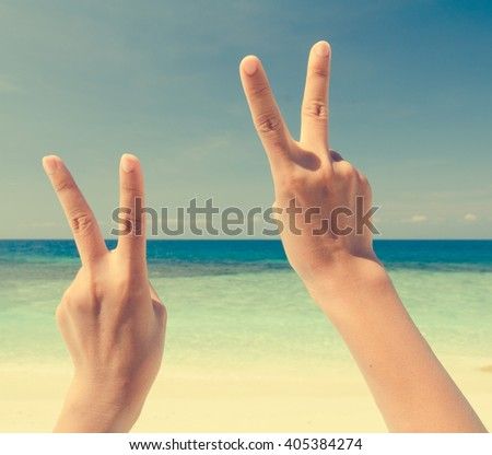 peace sign over beach in vintage retro tone - stock photo