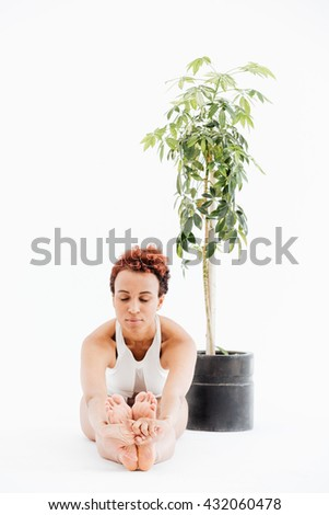 Peaceful african american young woman sitting near the tree in pot and doing yoga exercises over white background - stock photo