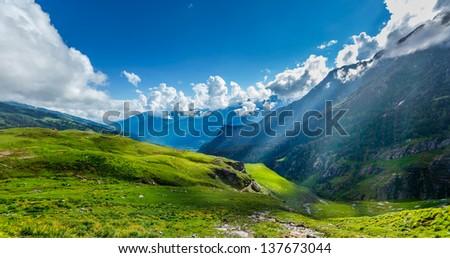 Peaceful alpine meadow mountain panorama in Himalayas with sun rays - stock photo