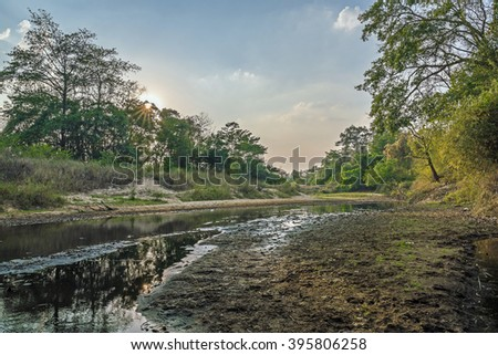 Peaceful and Tranquil nature background of beautiful river flowing through natural cascades and wet sand with sunlight shining gently - stock photo