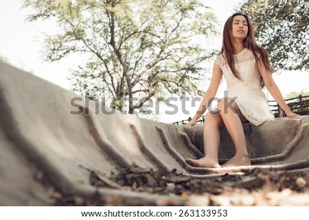 Peaceful Asian woman sitting in boat with her eyes closed