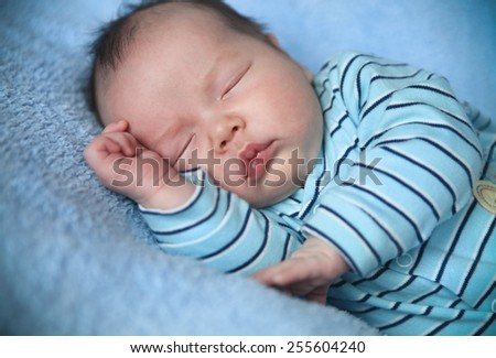 Peaceful baby lying on a bed while sleeping in a bright blue blanket - stock photo