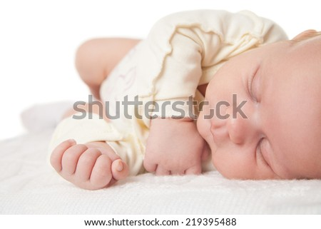 Peaceful baby lying on bed while sleeping in bright room - stock photo