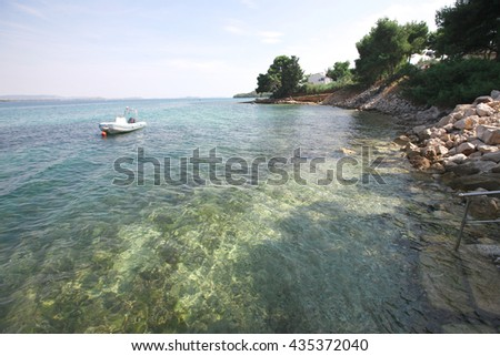 Peaceful bay with a ship floating on a sunny day - stock photo