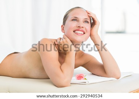 Peaceful blonde lying on towel smiling at the health spa