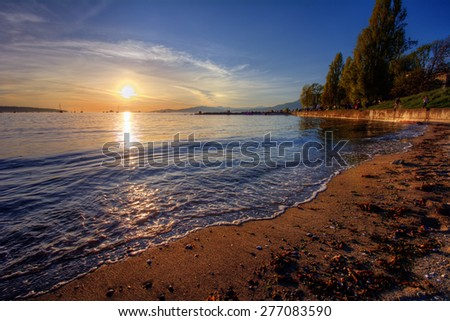 Peaceful bright sunset over sandy beach shore with distant cliffs - stock photo
