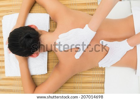 Peaceful brunette enjoying an exfoliating back massage in the health spa - stock photo