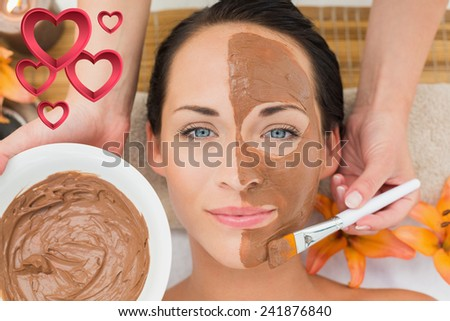 Peaceful brunette getting a mud facial applied against pink hearts - stock photo