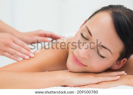 Peaceful brunette getting a salt scrub beauty treatment in the health spa - stock photo