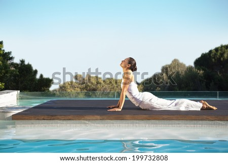 Peaceful brunette in cobra pose poolside on a sunny day at the spa - stock photo
